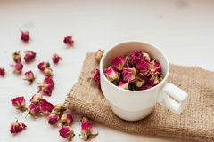 Cup and dry roses on the table. Bright colors and a white cup on a white table Royalty Free Stock Images