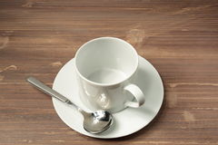Cup and empty white plate. Empty white cup and saucer on wooden background Stock Image