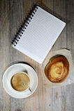 Cup of espresso, checkered notebook and bun Royalty Free Stock Image