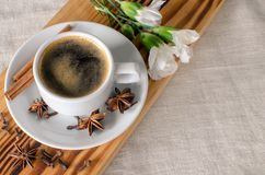 A cup of espresso, cinnamon sticks, anis stars and white carnations on wooden desk and textile background.  Good morning! Copy. A cup of espresso, cinnamon royalty free stock photos