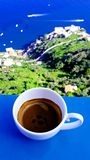 A cup of espresso on the sea, mountains and sky royalty free stock image