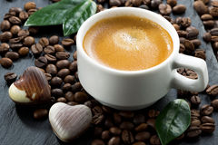 Cup of espresso on coffee beans background and chocolate candies Stock Image