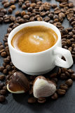 Cup of espresso, coffee beans background and chocolate candies Royalty Free Stock Photography