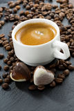Cup of espresso, coffee beans background and chocolate candies Stock Photography