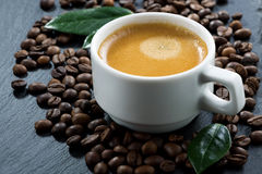 Cup of espresso on coffee beans background, selective focus Stock Image