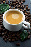 Cup of espresso on coffee beans background, vertical, close-up Royalty Free Stock Photo
