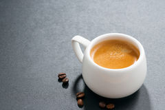 Cup of espresso and coffee beans on a dark background Stock Images