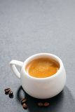 Cup of espresso and coffee beans on a dark background, vertical Royalty Free Stock Images