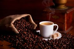 Cup of espresso with coffee beans on wooden table stock photography