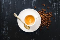 Cup of espresso coffee and beans on wooden black painted table Royalty Free Stock Photos