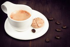 Cup of espresso coffee and biscuit near coffee beans, old style. Cup of espresso coffee and biscuit near coffee beans on old wood, old style Royalty Free Stock Photo