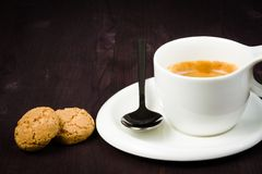 Cup of espresso coffee and biscuit near spoon. Cup of cup of espresso coffee and biscuit near spoon on old wood Royalty Free Stock Photo