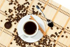 Cup of espresso coffee. Cup of espresso, cinnamon and candy. Coffee beans around the cup royalty free stock photo