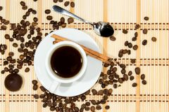 Cup of espresso coffee. Cup of espresso, cinnamon and candy. Coffee beans around the cup royalty free stock image