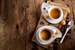 Cup of coffee on dark wooden background with small sweets stock photography