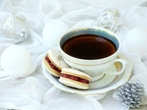 Cup of espresso coffee, French macaroons dessert on light background. Christmas and New Year cookies Stock Photos