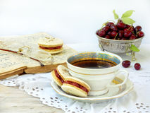 Cup of espresso coffee and French macaroons dessert stuffed with cornel. On light wooden background Stock Photos