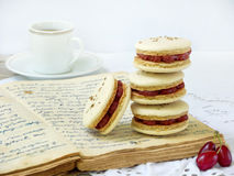 Cup of espresso coffee and French macaroons dessert stuffed with cornel. On light wooden background Stock Photo