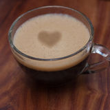 Cup of espresso coffee in glass with heart drawning on foam on wooden table background Royalty Free Stock Photos