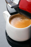Cup of espresso in the coffee machine close-up, vertical Royalty Free Stock Photos