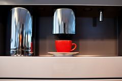 Red mug stands in a coffee machine. Cup of espresso from a coffee machine Stock Image