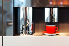 Red mug stands in a coffee machine. Cup of espresso from a coffee machine Stock Photo