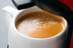 Cup of espresso in the coffee machine, selective focus, close-up Stock Photography