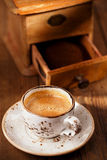 A cup of espresso coffee with Old coffee mill  textured table Royalty Free Stock Images