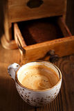 A cup of espresso coffee with Old coffee mill  textured table Royalty Free Stock Photography