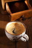 A cup of espresso coffee with Old coffee mill  textured table Stock Photography