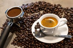 Cup of espresso coffee and portafilter on coffee beans background ,fresh espresso with crema perfect shot in the morning at cafe stock image