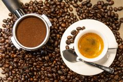 Cup of espresso coffee and portafilter on coffee beans background ,fresh espresso with crema perfect shot in the morning at cafe stock photos
