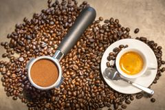 Cup of espresso coffee and portafilter on coffee beans background ,fresh espresso with crema perfect shot in the morning at cafe royalty free stock image