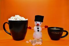 A cup of espresso coffee stands next to a funny snowman royalty free stock photography