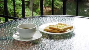 Cup of espresso coffee with toast. Put on a glass table Royalty Free Stock Images