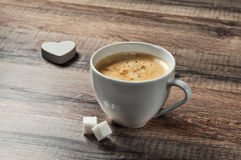 Cup of espresso coffee on a wooden table with sugar and wooden heart closeup Stock Photography
