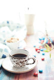 Cup of espresso with colorful sweets on wooden table Stock Images