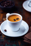 Cup of espresso crema with coffee beans Stock Image