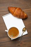 Cup of espresso, croissant and notepads, photo concept Royalty Free Stock Image