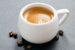 Cup of espresso on a dark background and coffee beans, close-up Stock Images