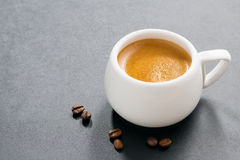 Cup of espresso on a dark background and coffee beans, top view Royalty Free Stock Photos