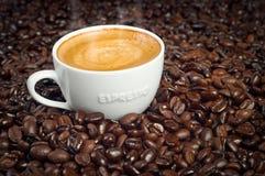 Cup Espresso in den dunklen gebratenen Kaffeebohnen Lizenzfreie Stockfotografie
