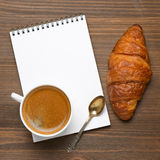 Cup of espresso, fresh croissant and notepads, photo concept, to Royalty Free Stock Images