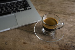 Cup of espresso with laptop on wooden table. Stock Images