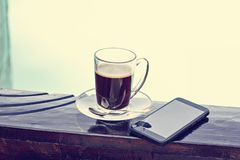 A cup of espresso and mobile phone and a pool in the background. Morning coffee. Summer Breakfast. Coffee at the resort royalty free stock image