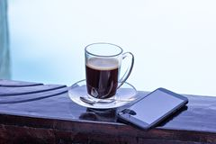A cup of espresso and mobile phone and a pool in the background. Morning coffee. Summer Breakfast. Coffee at the resort royalty free stock photo