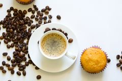 Cup of espresso with muffins and coffee beans on white table Royalty Free Stock Images