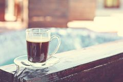 A cup of espresso and a pool in the background. Morning coffee. Summer Breakfast stock images