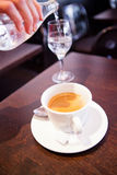 Cup of espresso and pouring water Royalty Free Stock Images