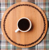 Cup of espresso on round wooden board with circuit of the coffee beans. On plaid background. Coffee in white cup on round wooden cutboard with circuit of the stock images